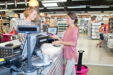 smiling woman paying with credit card in supermarket