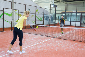 couple playing tennis game indoor