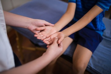 Midsection of female therapist examining hands with boy sitting