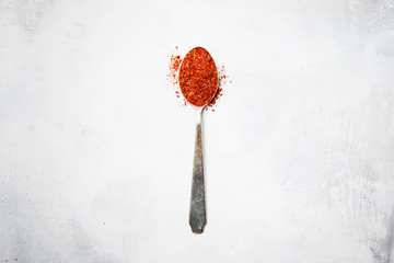 Ground red hot chili pepper in spoon, top view