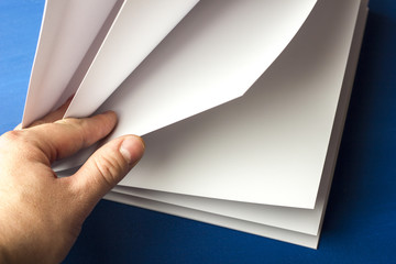 Empty white paper for notes, notebook, diary, booklet, organizer in hand on a blue background. Advertising, materials, education, text, the concept of space for copying. Layout