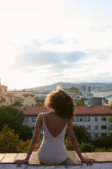 Back view of mulatto brunette in dress watching cityscape on border