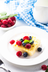 Cheesecake with fresh berries on white plate. Healthy breakfast.