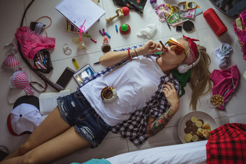 after studying blonde student, lying on the floor in headphones and sunglasses, listening to music and smoking a cigarette. The image of a modern student, education, Accessories of a modern young girl