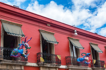 Fototapete - Red Building and Alebrije