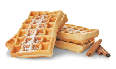 Tasty homemade waffles with sugar powder and cinnamon sticks on white background