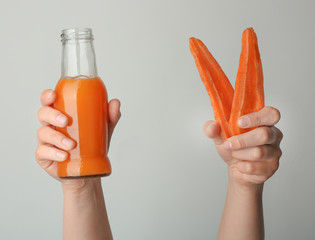 Woman holding bottle of fresh juice and carrot slices on light background
