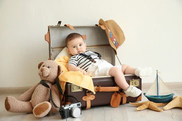 Cute little boy lying in suitcase. Concept of baby holiday