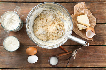 Cooking dough for vanilla cake on wooden background