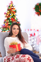 Attractive young lady with gift box at home