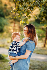 Mom holds a small boy in the arms on an autumn background. Concept mum and son, childhood, happy wife.