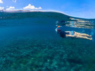 Woman swimming in blue sea. Snorkeling girl in full-face snorkeling mask.