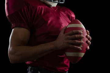 American football player holding a ball in one hand