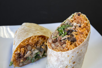 Two halves of a carne asada burrito on a plate