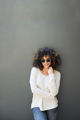 Beautiful smiling mulatto with afro in round sunglasses