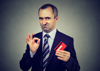 Sly liar mature businessman employee reassuring their credit card is the best