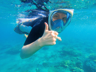 Snorkeling woman shows thumb. Snorkeling girl in full-face snorkeling mask.