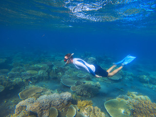 Male snorkel in tropical lagoon undersea photo. Snorkeling in coral reef. Summer holiday activity.