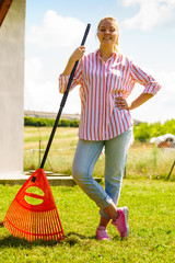 Woman using rake to clean up garden