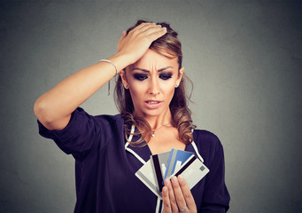 Confused stressed young woman looking at too many credit cards