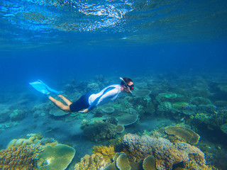 Young snorkel swims underwater. Male snorkel in tropical lagoon undersea photo.