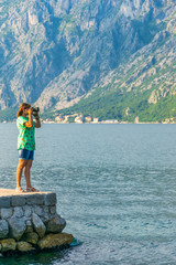 An attractive girl is taking pictures of the seascape.