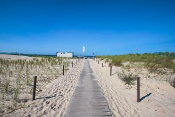 Beautiful summer vibrant view of Warnemunde, Rostock, Germany, popular german seaside resort, with beach, seashore and lighthouse