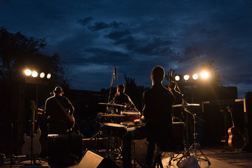 Backlit shot of a small rock band in concert