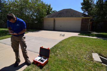 Farmers Insurance claims adjuster Brent Hazen programs the flight path for a Kespry drone to assess a home damaged by Hurricane Harvey in Missouri City Texas