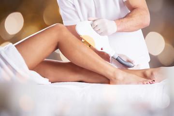 Laser Treatment At Beauty Clinic On Woman's Leg
