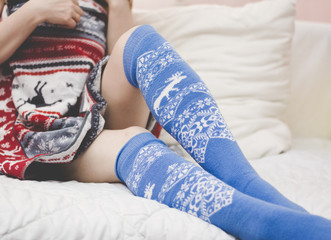 Girl legs on the bed in the Norwegian winter socks and a towel.