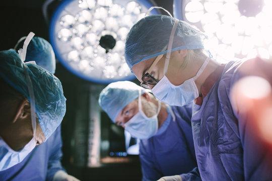 Concentrated surgeon performing surgery with her team