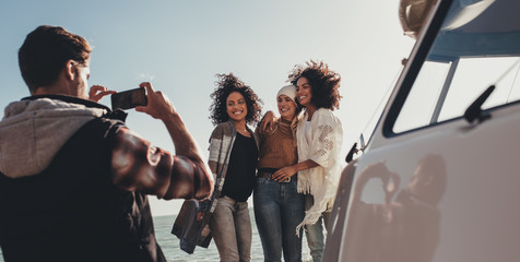 Group of young people on road trip taking pictures