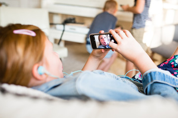 Girl wearing headphones while looking at self image on mobile device