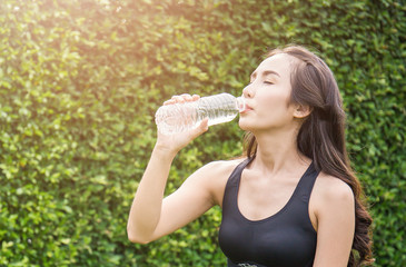 Asian young woman drinking water after exercise, asian athlete drinking a bottle of water over green leaves garden background