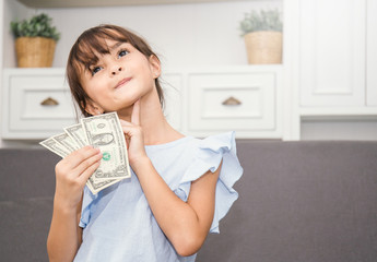 Cute little girl holding money in the living room, pretty girl thinking about how to spend her saving