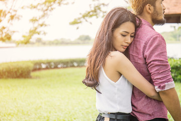 couple hugging outdoors at the park, young woman hugging man, breaking up