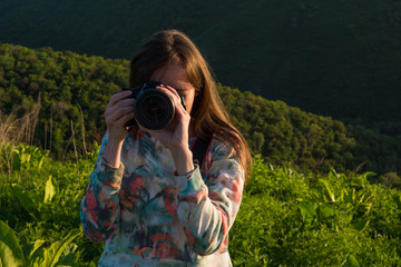 Girl take photo with big camera in nature
