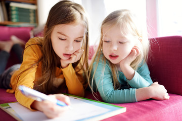 Two cute little sisters writing a letter together at home. Older sister helping youngster with her homework.