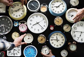 Closeup of hands holding clocks