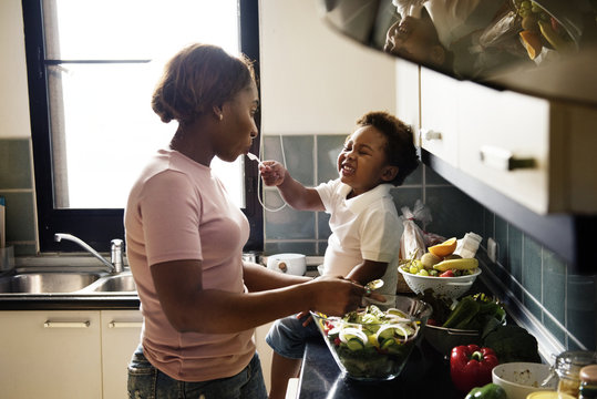 Black kid feeding mother with cooking food in the kitchen