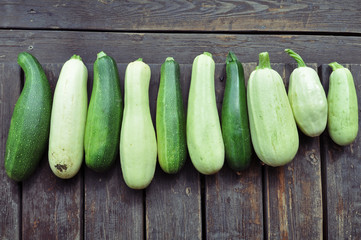 Many ripe squash and zucchini on a brown wooden surface top view.