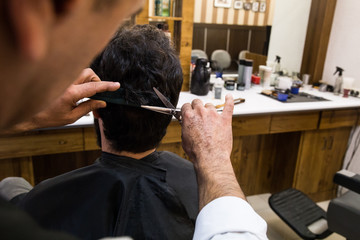 Crop barber using scissors and cutting hair of anonymous customer in chair.