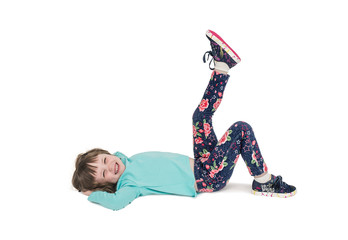 A little girl in sports clothes is lying on the floor and is engaged in gymnastics. White isolated background.
