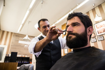 Adult content barber cutting hair of customer in chair doing modern haircut.