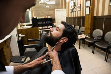 Anonymousstylist taking care of male client's beard cutting it with scissors.