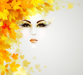 Beautiful woman face is in autumn circle of yellow and orange leaves on the light background.