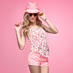 Fashion. Model Girl in Stylish Pink Outfit. Blond woman Having Fun Smiling. Fashion Sunglasses, Glamour Pink Shorts, Floral Top. Playful Hipster, Trendy pink fashion Hat, Funny summer Hairstyle