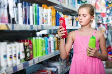 Girl teenager choosing shampoo and conditioner at shop