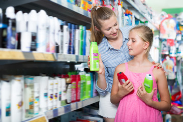 Adult woman with girl choosing shampoo